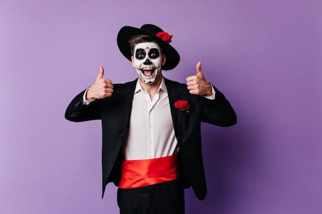 Émotionnel jeune homme en costume classique et ceinture de satin rouge leva joyeusement les pouces.