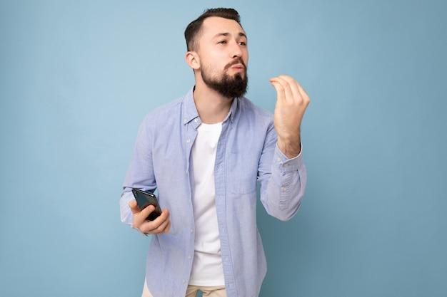 Émotionnel positif beau jeune homme barbu brunet portant une chemise bleue décontractée et un t-shirt blanc en équilibre isolé sur fond bleu avec un espace vide tenant à la main un téléphone portable à la recherche de la tr