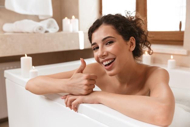 Émotionnelle excitée belle femme dans la salle de bain se trouve au repos dans la baignoire montrant le geste de pouce en l'air.