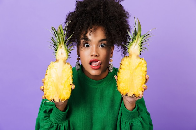 Émotionnelle excitée jeune jolie femme africaine isolée sur espace violet tenant ananas léchant sa lèvre.