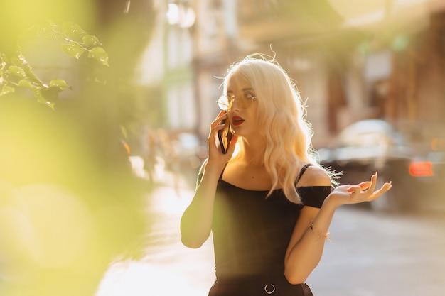 Émotionnelle fille blonde à lunettes de soleil avec téléphone au soleil de l'été