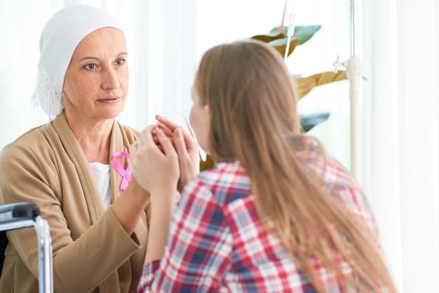 Émotionnelle de la jeune fille blanche caucasienne avec espoir et sourire visitant et encourager à soutenir sa mère qui se bat avec la chambre d'hôpital du cancer du sein, campagne de ruban de sensibilisation au cancer du sein.