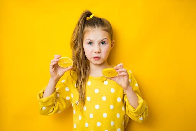 Émotionnelle jeune fille avec citron coupé sur fond jaune, espace pour le texte