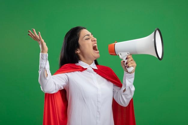 Émotionnelle jeune superwoman debout en vue de profil en criant dans le haut-parleur à tout droit isolé sur mur vert