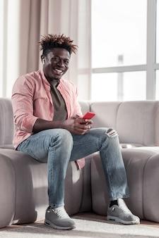 Des émotions bienveillantes. joyeux homme assis sur un canapé et écoutant de la musique