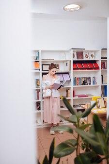 Émotions détendues. brune concentrée inclinant la tête en lisant un livre