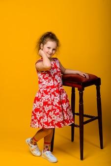 Émotions de l'enfant insouciant heureux. énergique joyeuse adorable petite fille riant de blague sur fond jaune.