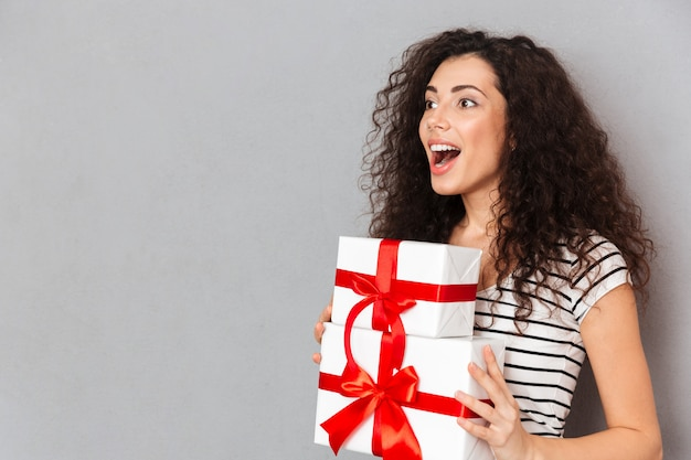 Émotions heureuses de belle femme en t-shirt rayé tenant deux boîtes emballées avec des arcs rouges en se tenant sur un mur gris