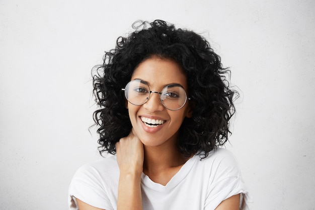 Émotions humaines positives. portrait de belle et charmante étudiante avec une coiffure afro, ayant un regard timide, riant, portant des lunettes rondes élégantes, touchant son cou avec la main