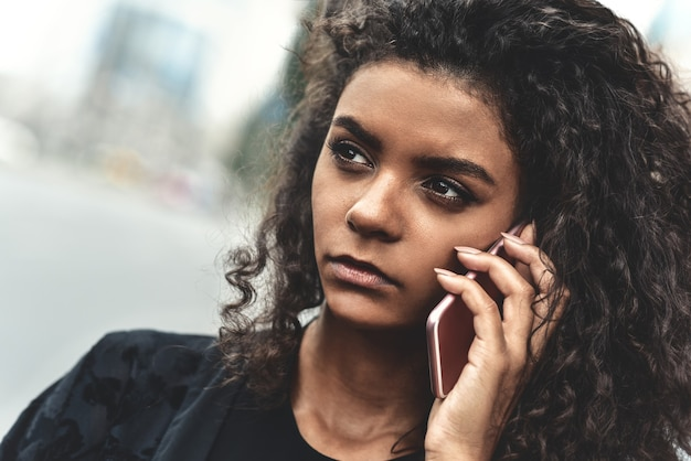 Émotions négatives. concept de mode de vie. gros plan d'une jeune femme métisse utiliser un téléphone.