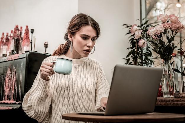 Émotions pendant le travail. la pigiste est émotive lorsqu'elle travaille dans un café avec son ordinateur