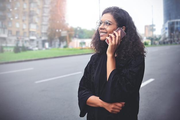 Émotions positives. concept de mode de vie. gros plan d'une jeune femme métisse utiliser un téléphone.
