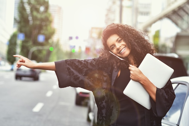 Émotions positives. une femme métisse heureuse utilise un téléphone, essayez de prendre un taxi. image filtrée