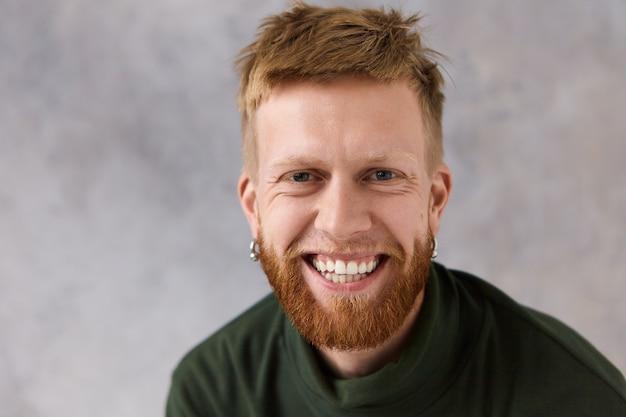Émotions, sentiments et réactions humaines sincères. beau jeune homme charismatique avec des boucles d'oreilles et une barbe épaisse riant de blague, étant de bonne humeur, souriant largement, montrant ses dents