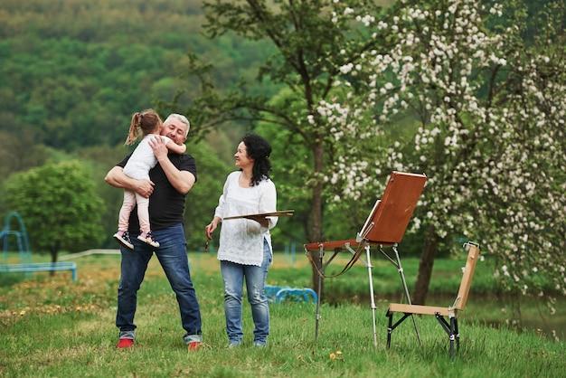 Émotions sincères. grand-mère et grand-père s'amusent à l'extérieur avec leur petite-fille. conception de peinture