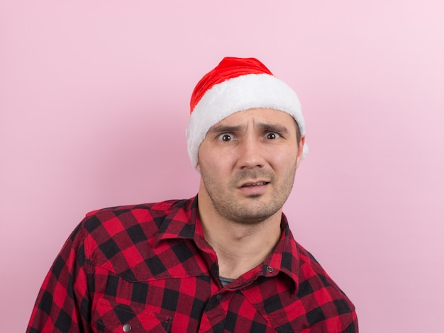 Émotions sur le visage, indifférence et dégoût. un homme dans un lapin à carreaux et un chapeau de noël rouge