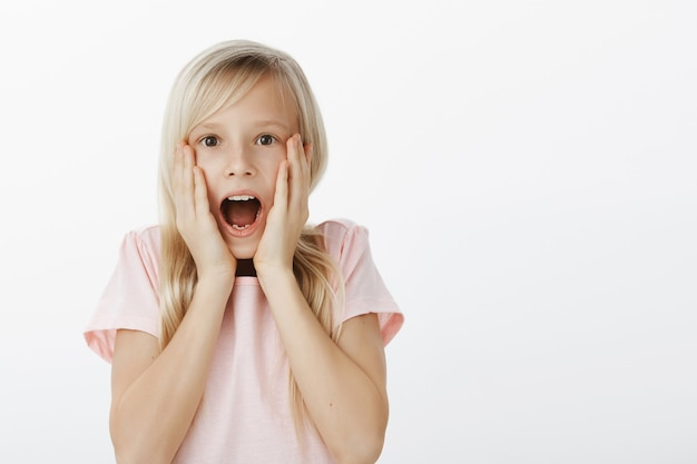 Émotive bouleversée adorable enfant de sexe féminin aux cheveux blonds narutaux, hurlant de surprise et d'émotions, choquée et étonnée, tenant les paumes sur les joues, voyant quelque chose d'incroyable