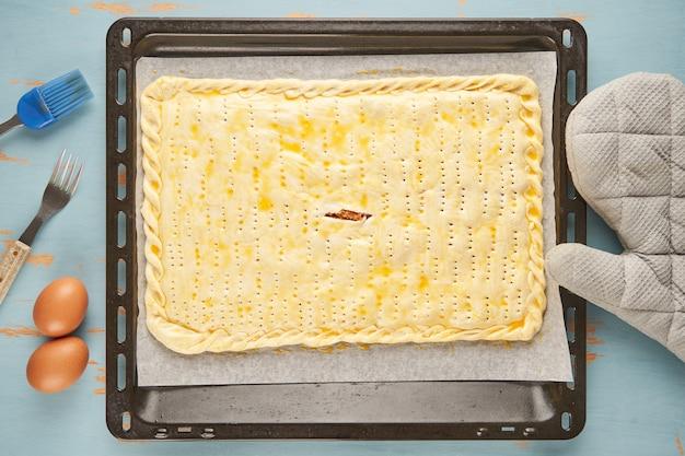 Empanada crue typique de galice farcie au thon est sur une plaque à pâtisserie