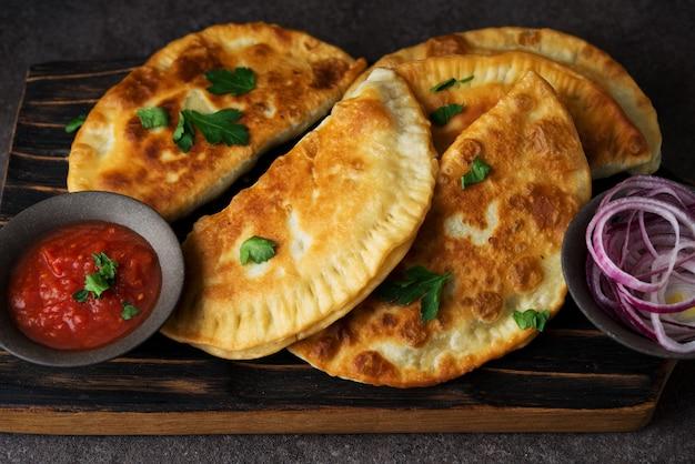Empanadas frites maison au porc, chebureks aux champignons sur une planche de bois