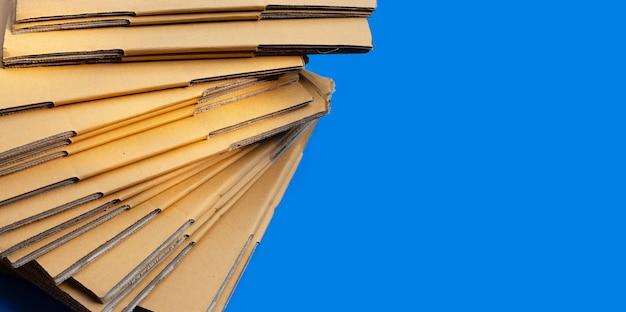 Empilage de boîtes en carton, papier ondulé sur fond bleu. copier l'espace
