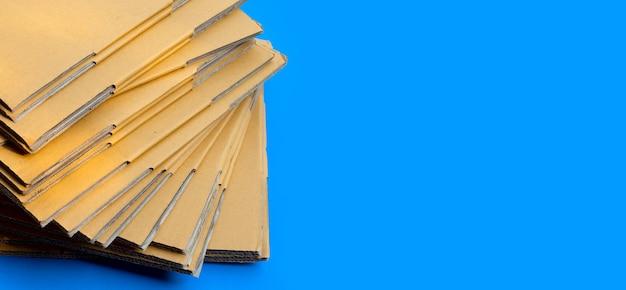 Empilage de boîtes en carton, papier ondulé sur fond bleu.