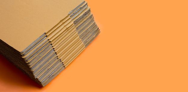 Empilage de boîtes en carton, papier ondulé sur fond orange. copier l'espace