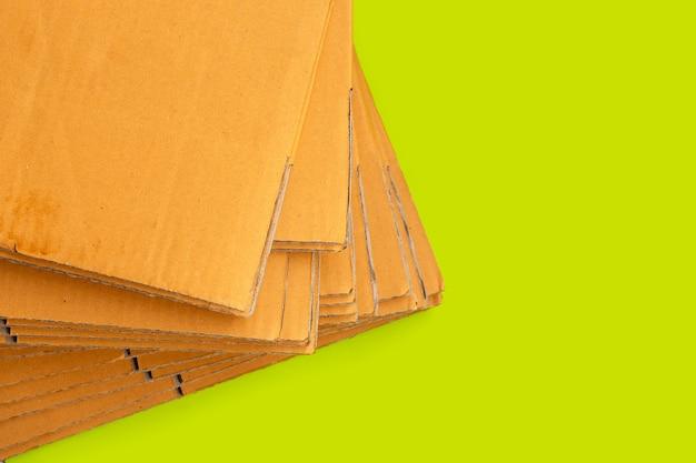 Empilage de boîtes en carton, papier ondulé sur fond vert.