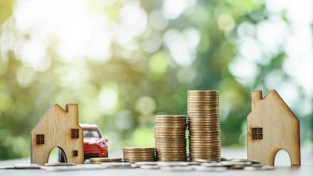 Empilant des pièces de monnaie avec une maison et une voiture model.save et investissement pour acheter le concept de maison.