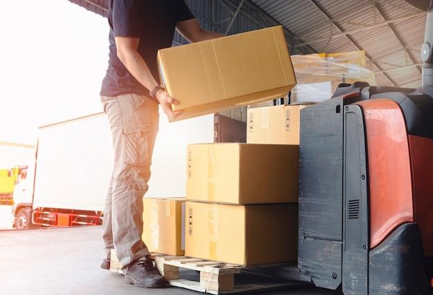 Empilement de boîtes de colis de levage de courrier de travailleur sur des boîtes d'expédition de livraison de palette logistique d'entrepôt