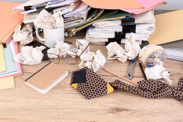 Empiler les documents et remonter les trombones sur le bureau en bois du bureau.