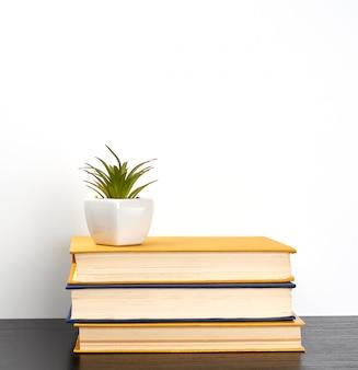 Empiler des livres sur une table noire, sur un pot en céramique