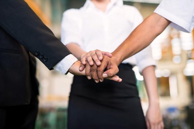 Empiler les mains pour un travail d'équipe en usine