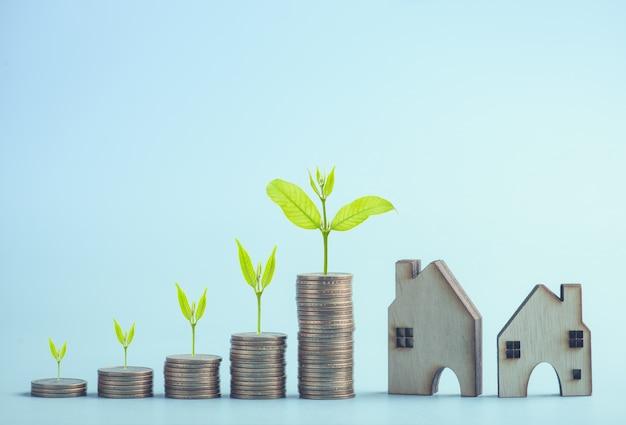 Empiler des pièces de dollars et un arbre vert poussant avec un modèle de maison
