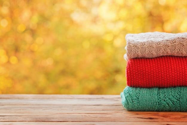 Empiler des tas de vêtements d'automne tricotés sur la nature.