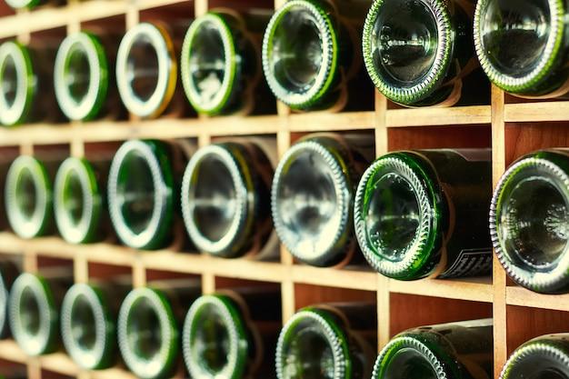 Empilés de vieilles bouteilles de vin dans la cave