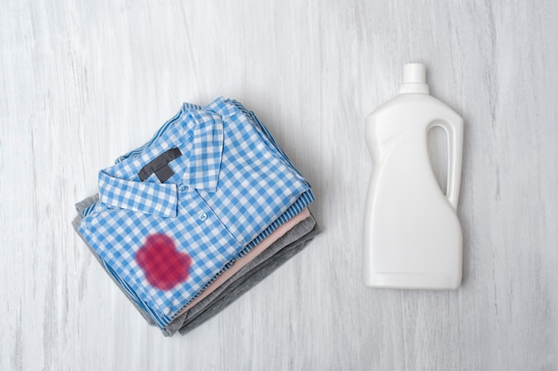 Empilez du linge sale pliable et une bouteille de liquide pour le lavage. vue de dessus