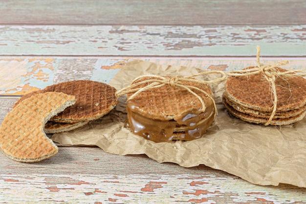 Empilez les stroopwafels sur du papier brun, à côté d'un autre biscuit avec une bouchée (vue latérale).