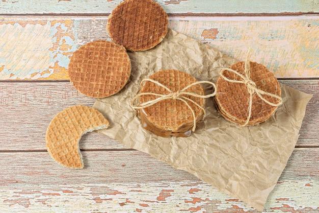 Empilez les stroopwafels sur du papier brun, à côté d'un autre biscuit avec une morsure.