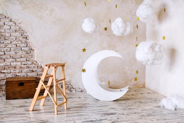 Emplacement pour enfants pour une séance photo. lune avec décor rêveur d'étoiles et de nuages. éléments de l'intérieur.