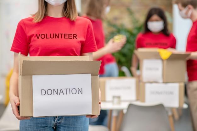 Emploi, bénévolat. fille bénévole en tshirt rouge avec l'inscription tenant une boîte en carton de don et des amis avec des masques de protection derrière l'emballage