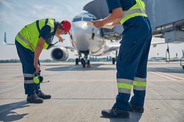 Employé de l'aéroport vêtu d'un uniforme montrant l'avion garé à son collègue de race blanche