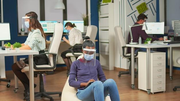 Employé africain avec masque de protection contre la pandémie de covid-19 assis sur un pouf au milieu d'une salle de bureau tenant une tablette numérique. équipe commerciale multiethnique travaillant dans le respect de la distance sociale
