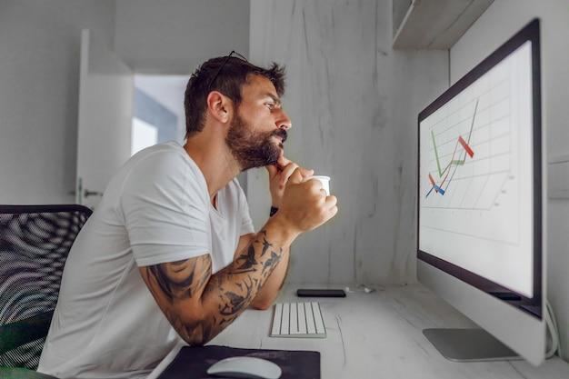 Employé assis dans son bureau à domicile et analysant le graphique pour le marché boursier.