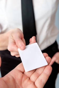L'employé de la banque offre une carte en plastique, gros plan, espace copie. femme d'affaires montrant une carte de crédit ou une carte de visite en plastique