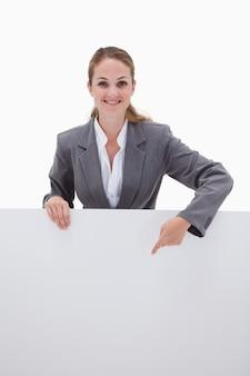 Employé de banque souriant pointant vers le bas à une pancarte blanche sur un fond blanc