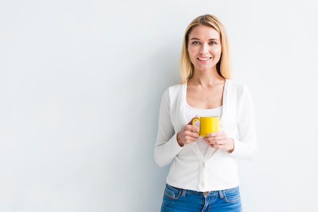Employé blonde tenant une tasse sur fond blanc