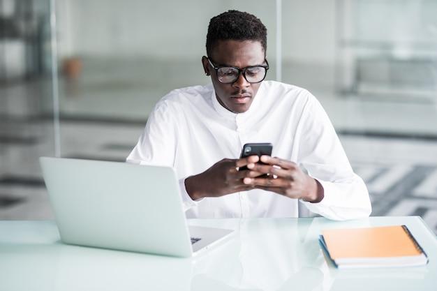 Employé de bureau beau avoir quelques minutes de pause, envoyer des sms sur un téléphone intelligent