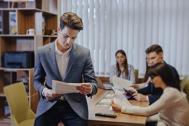 Employé de bureau élégant dans une veste lit le papier, s'appuyant sur une table et sur le fond de ses collègues