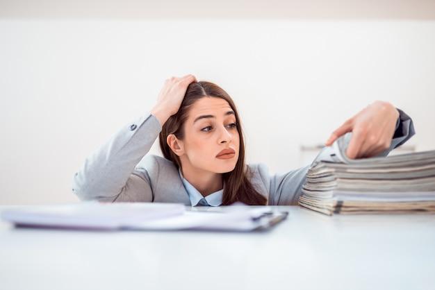 Employé de bureau épuisé avec une pile de dossiers.