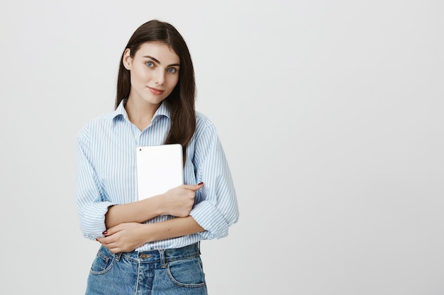 Employé de bureau féminin attrayant tenant une tablette numérique et souriant